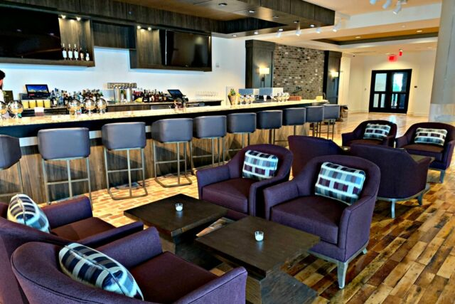 indoor bar with stools and lounge seating in front of it