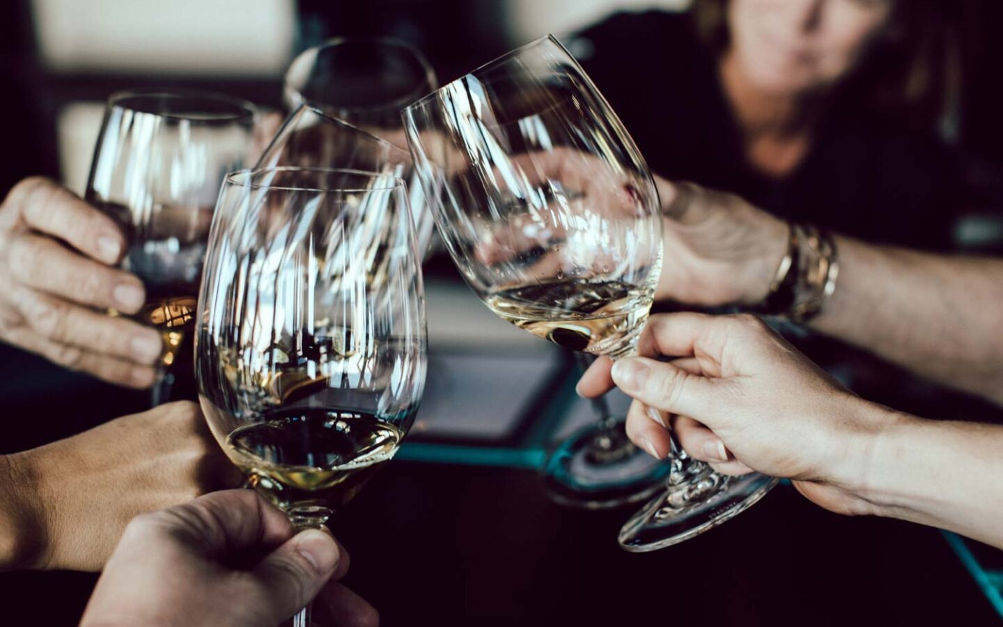 closeup of people clinking their glasses of wine
