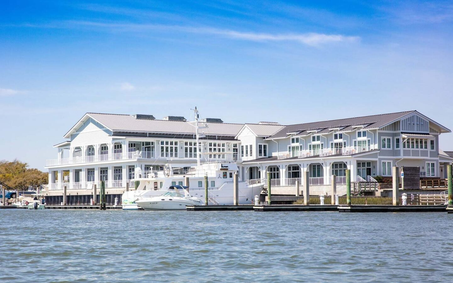 large white restaurant building on a body of water with docked boats next to it