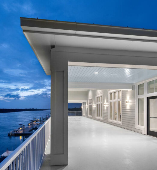 large white balcony at night time overlooking a body of water