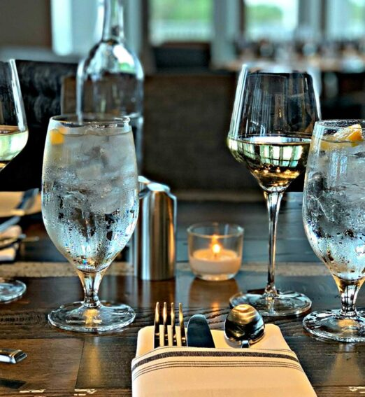 closeup of clear glasses of water and wine on a wooden dining table