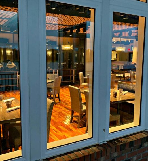 view of the inside of a restaurant dining room through large windows