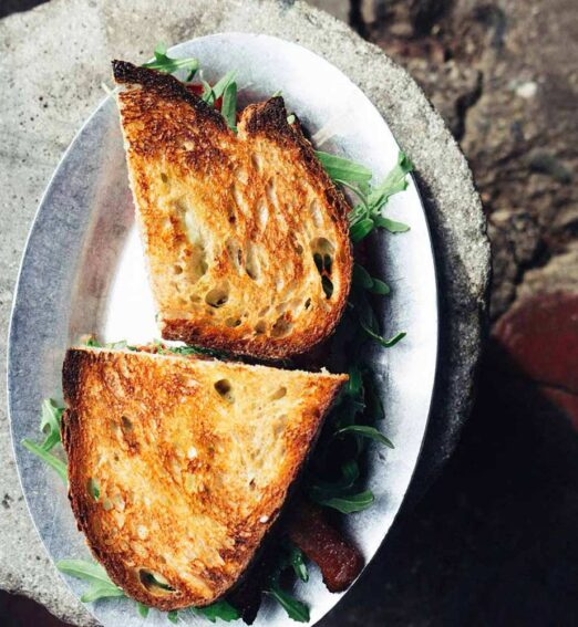 overhead view of a grilled toast sandwich on a steel plate