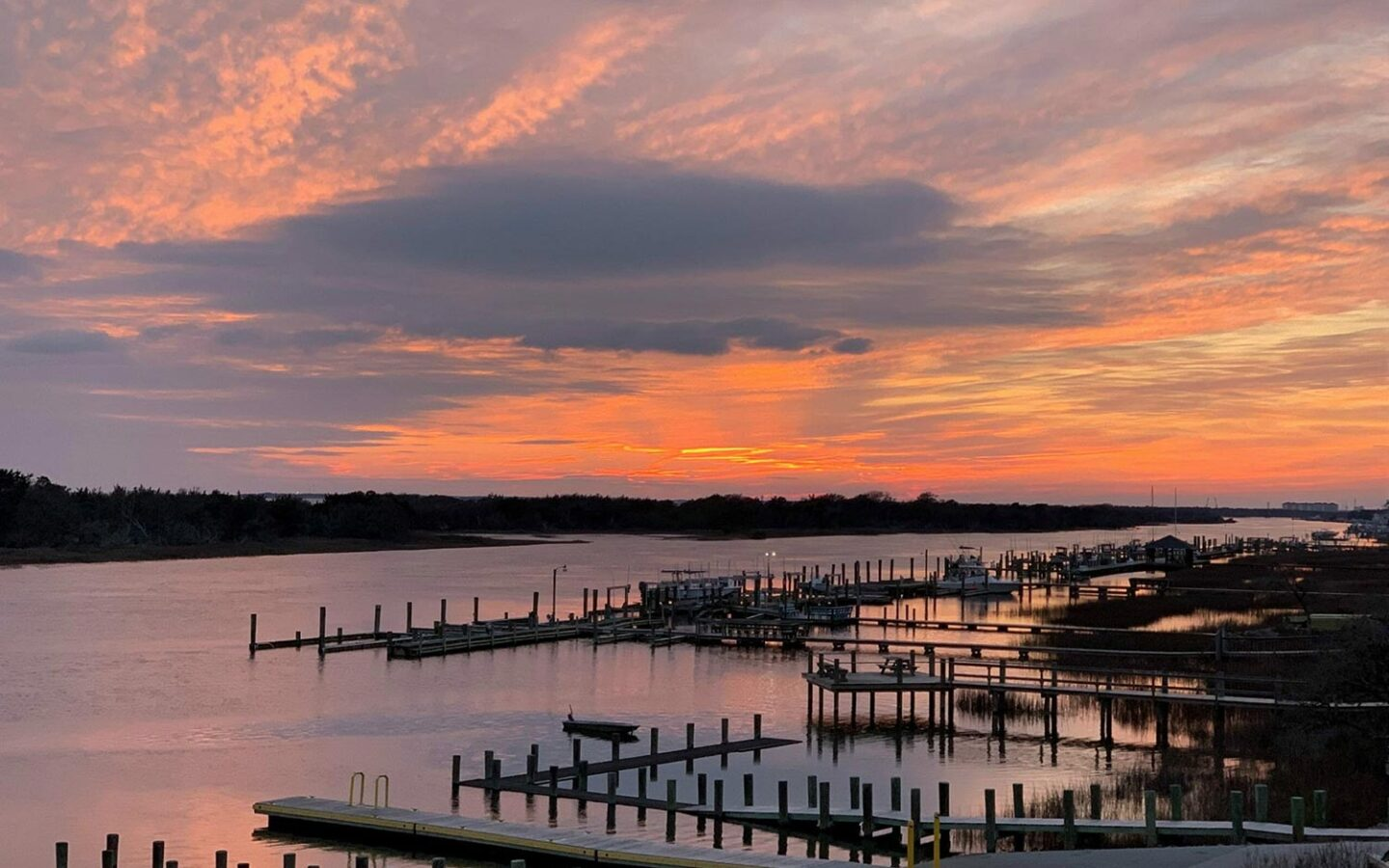 view of a long and wide river with many docks on the edge during sunset