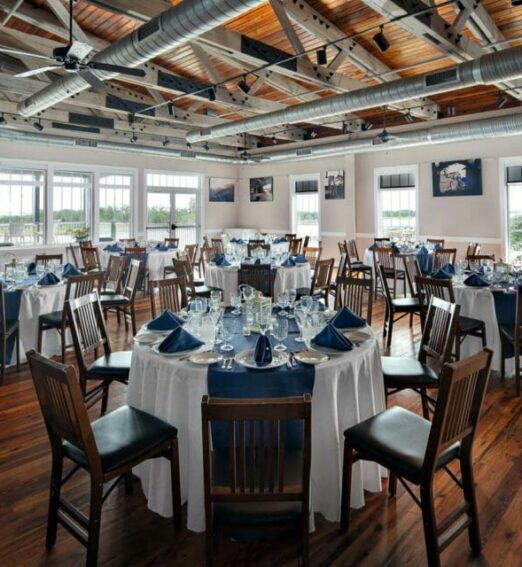 restaurant dining room with large windows and wooden flooring with round tables and wooden chairs