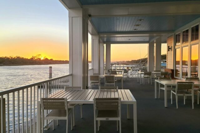outdoor balcony dining area on the side of a body of water during sunset