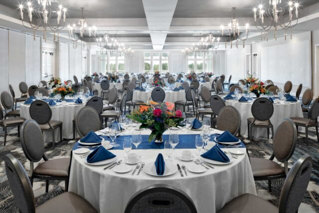 indoor venue with some windows and round tables with cushioned chairs